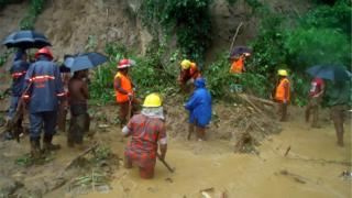 Bangladeshi fire fighters search for bodies after a landslide in Bandarban on 13 June 2017