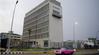 A car with tourists drives past the US Embassy in Havana