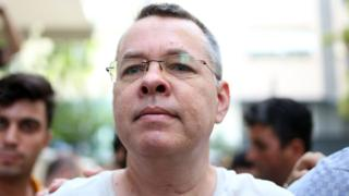 Pastor Andrew Craig Brunson is escorted by Turkish plain clothes police officers as he arrives at his house in Izmir, Turkey, 25 July 2018