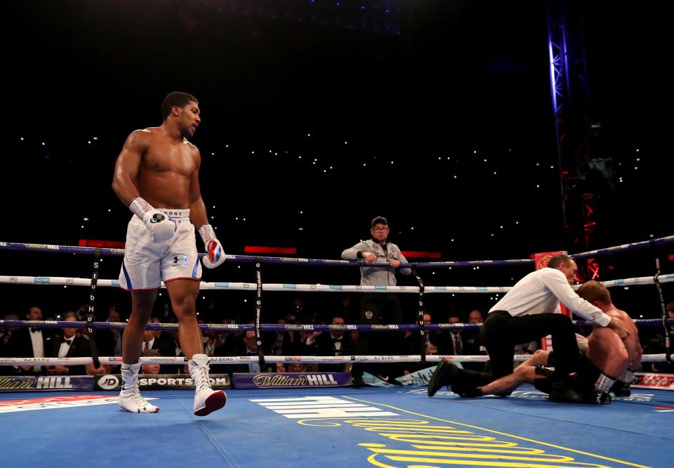 Anthony Joshua walks away as Alexander Povetkin falls to the canvas