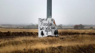 A handwritten sign is seen on a telephone pole on the road to Paradise, California, U.S. November 21, 2018
