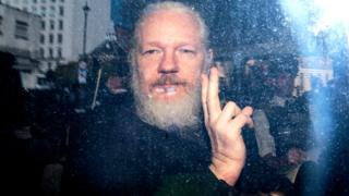 Julian Assange gestures to the media from a police vehicle on his arrival at Westminster Magistrates court on 11 April 2019