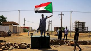 """A Sudanese protester holds a national flag as he stands on a barricade along a street, demanding that the country""""s Transitional Military Council hand over power to civilians, in Khartoum, Sudan June 5, 2019."""