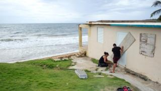 A couple board up the door of their beachfront house as Tropical Storm Dorian approaches in Yabucoa, Puerto Rico