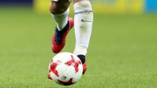 A Chilean player kicking a football