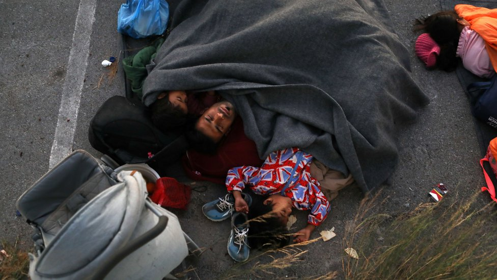 Migrants leave the remains of Moria refugee camp