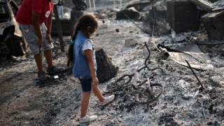 A little girl looks at a burnt bicycle in Phoenix, Oregon