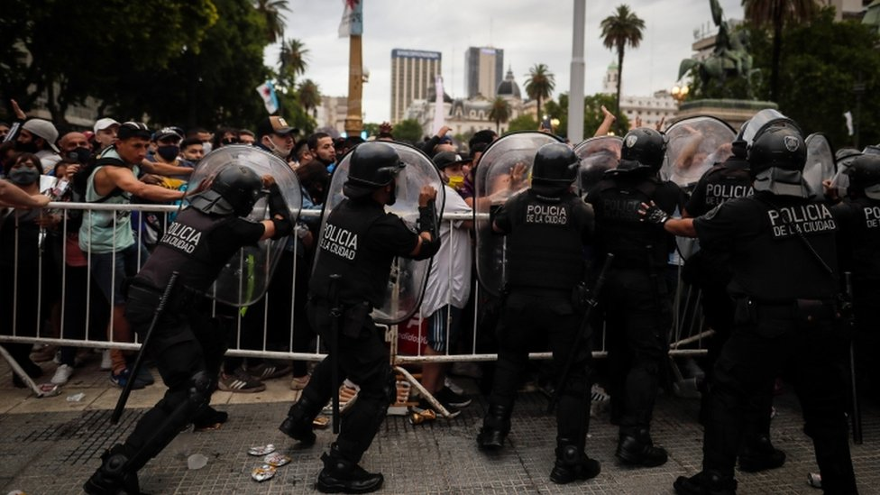 fans confront police as they wait to visit the coffin of Maradona